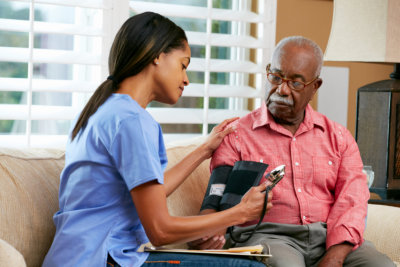 nurse checking the blood pressure of the old man